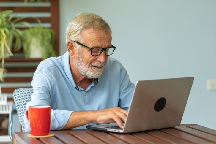 Gentleman using laptop with cup of tea next to him